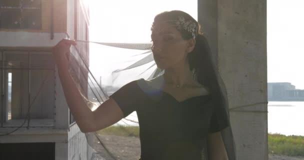 junge Frau hebt Hände mit Schleier gegen Stadtbild