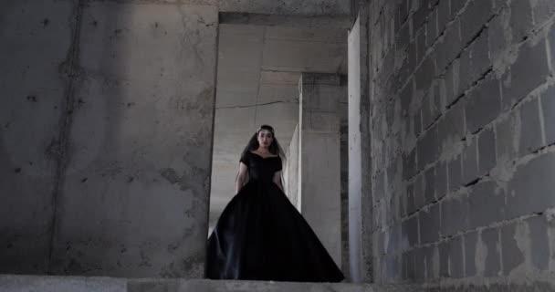 Reiterin im schwarzen offenen Schulterkleid betritt grauen Raum