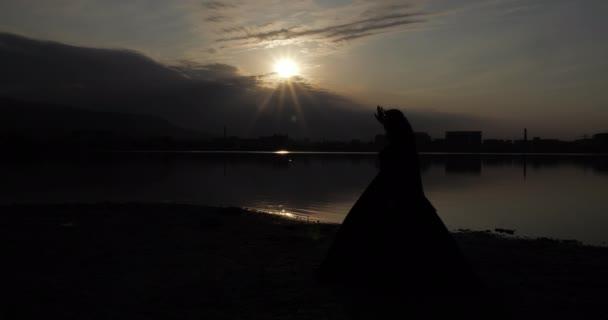 vékony lovas nő köntösben sziluett áll a strandon naplementekor
