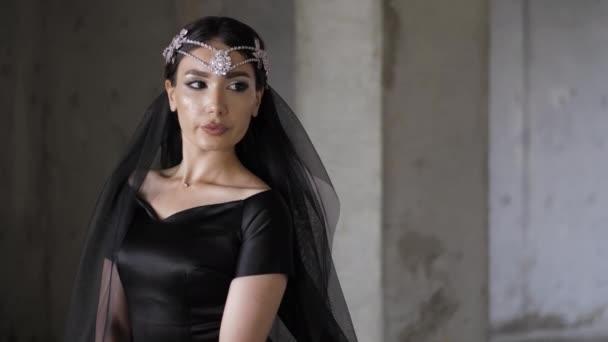 ernste Dame im schwarzen Kleid mit Diamant-Diadem und Schleier