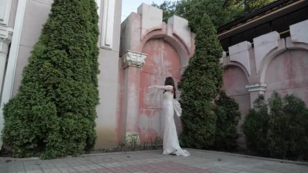 atraktivní nevěsta v dlouhé těsné svatební šaty se otáčí kolem