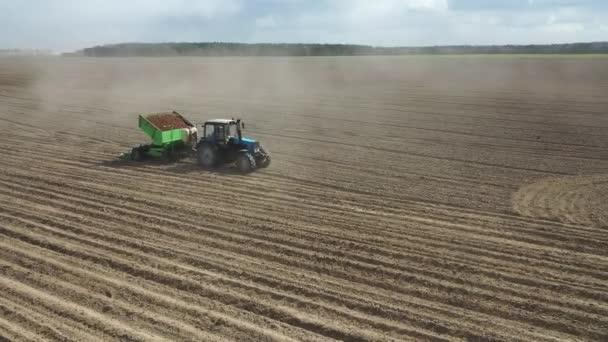 GRODNO, BELARUS - ÁPRILIS 2020: Egy mezőgazdasági termelő és traktor a szántóföldön burgonyát ültet a termékeny mezőgazdasági területeken. Légi felvétel.