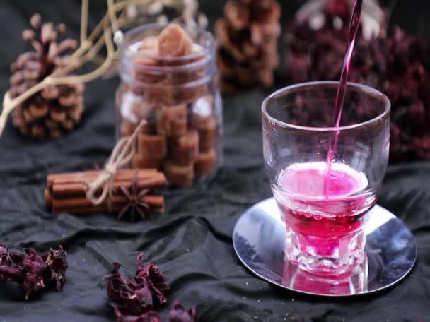 Lassú mozgás: A Roselle tea (Jamaica sorrel, Rozelle vagy hibiscus sabdariffa) közeli felvételét egy vízforralóból száraz rozellával és barna nádcukorkockával töltött üvegpohárba öntjük. Egészséges gyógynövény tea gazdag C-vitamin szelektív Focus.