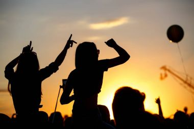 Girls with hands up dancing, singing and listening the music during concert show on summer music festival