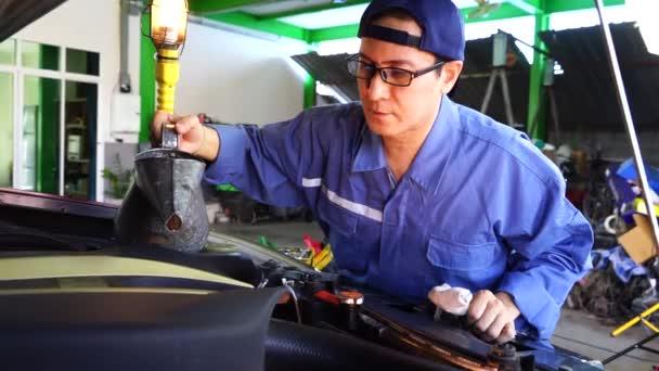 Mechanik v modré uniformě ležící a pracující pod autem v autoservisní garáži.Koncept servisu a údržby vozidla