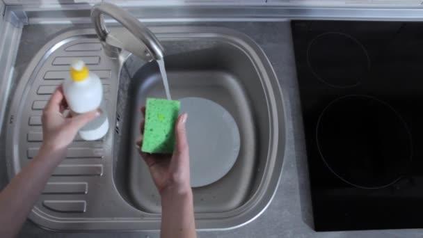 Hospodyně umývá v kuchyni bílý talíř. Vystěhování v bytě