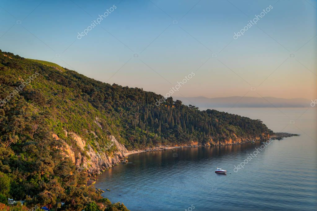 View from the top of mountains of Buyukada island, Marmara Sea, Istanbul, Turkey, with green woods, calm sea, and clear sky at sunset