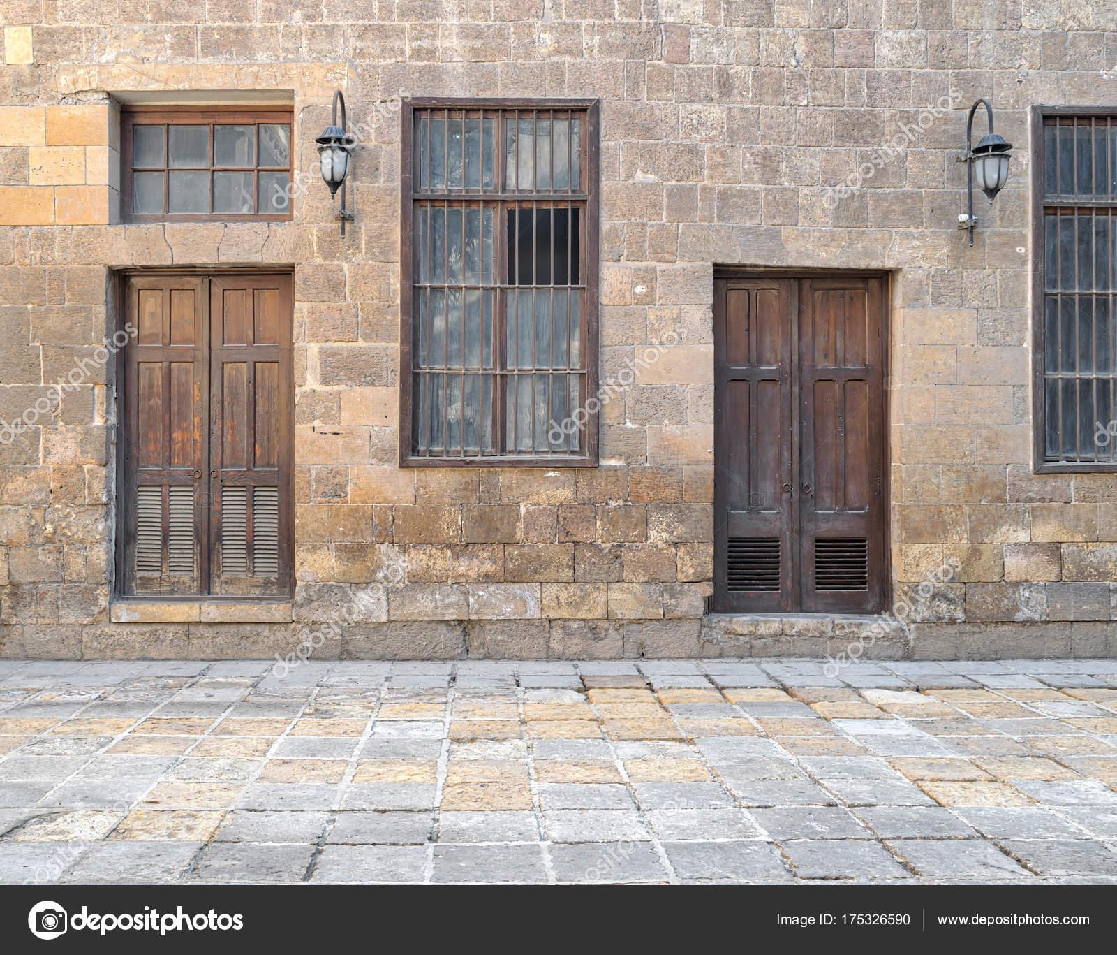 Fachada Abandonada De La Vieja Pared De Ladrillos De Piedra Con Puertas De  Madera, Ventanas