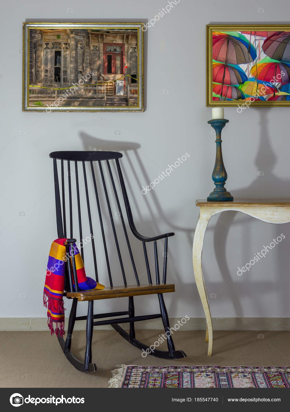 vintage gunga stol, gammal stil bord, ljusstake på bakgrund av off