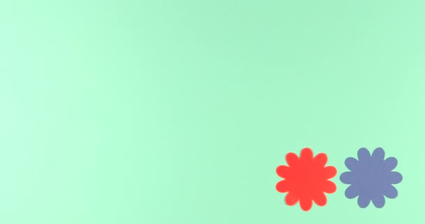 Animated stop motion background  frame of blooming paper flowers on a colored background.
