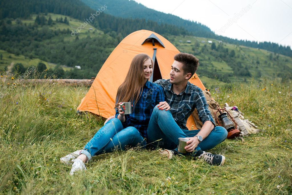 Guy and girl lovers tourists relax and admire beautiful mountain scenery