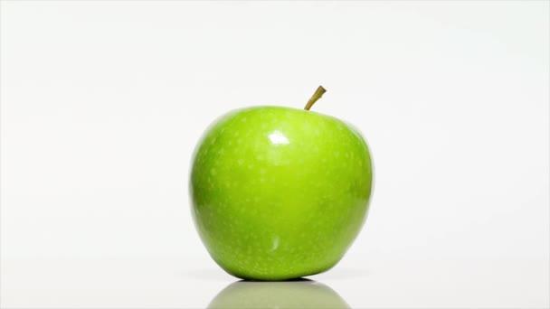 Zelené jablko se stínem na bílém stole, otáčení o 360 stupňů. Bílé pozadí.Ultra vysoké rozlišení 3840x2160.4k rozlišení