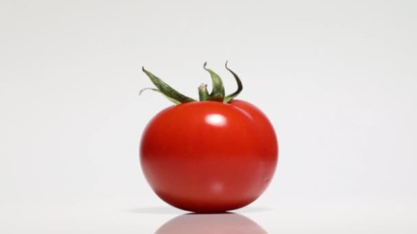 Červené rajče se stínem na bílém stole, otáčení o 360 stupňů. Bílé pozadí.Ultra vysoké rozlišení 3840x2160.4k rozlišení