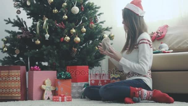 Young beautiful girl wraps a Christmas gift