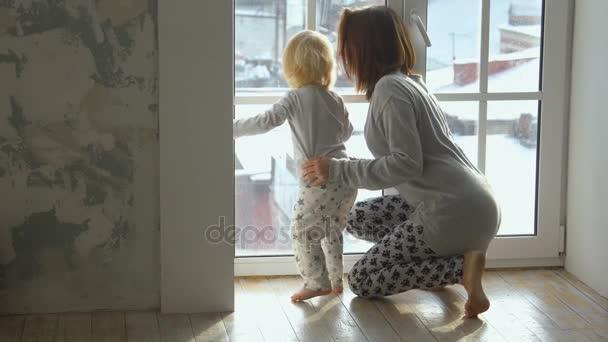 Malé dítě a její matka se dívala z okna