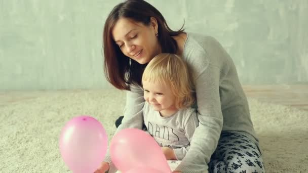 Matka a její malá dcera si hraje s balónky