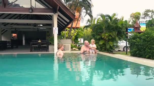 Grandparents with granddaughter in swimming pool