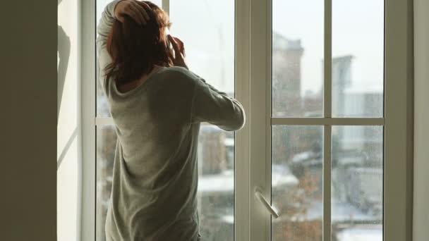 Frau mit Smartphone steht neben breitem Fenster