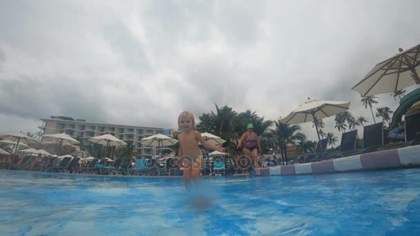 Mädchen spritzt Wasser im Schwimmbad