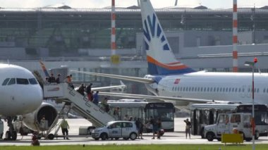 Passengers walk on gangway after approaching at Dusseldorf International Airport.