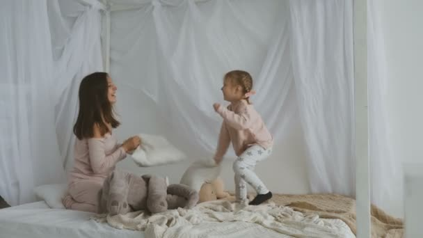 Mother and little daughter play with pillows