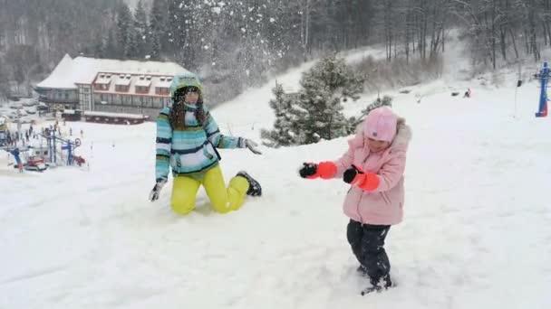 Frau und kleines Mädchen werfen Schnee