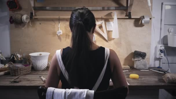 Woman works in pottery workshop