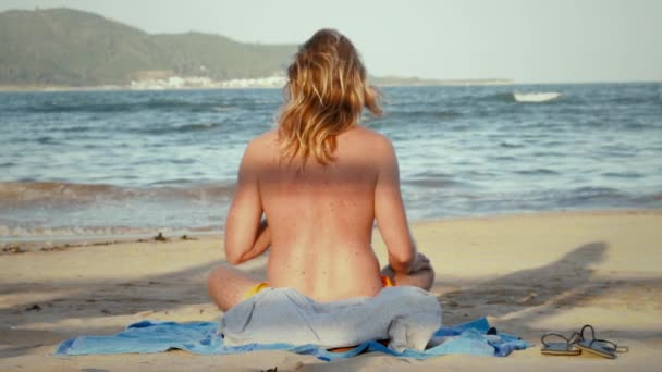 Young man in yoga pose on the beach