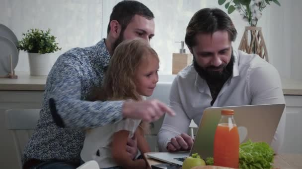 Gay Couple With Daughter Looking At Laptop