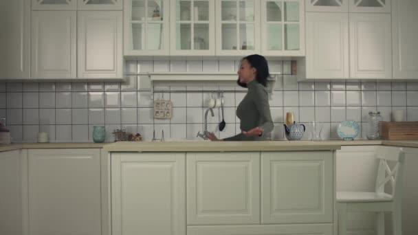Rozkošná africká americká žena tančí v kuchyni doma