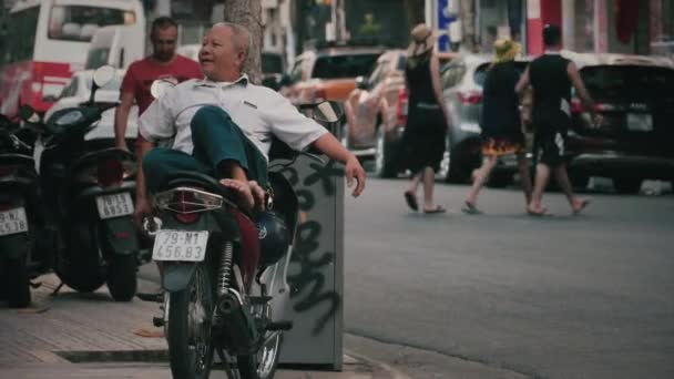 Middle-aged vietnamese man lies on a motorcycle
