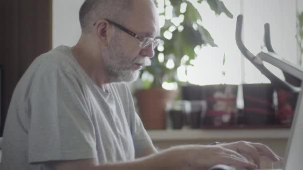 Porträt eines älteren Mannes, der zu Hause Laptop benutzt