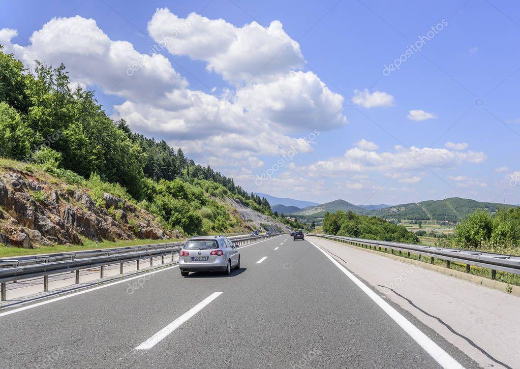 Cars speeding on the Autobahn among mountain scenery.