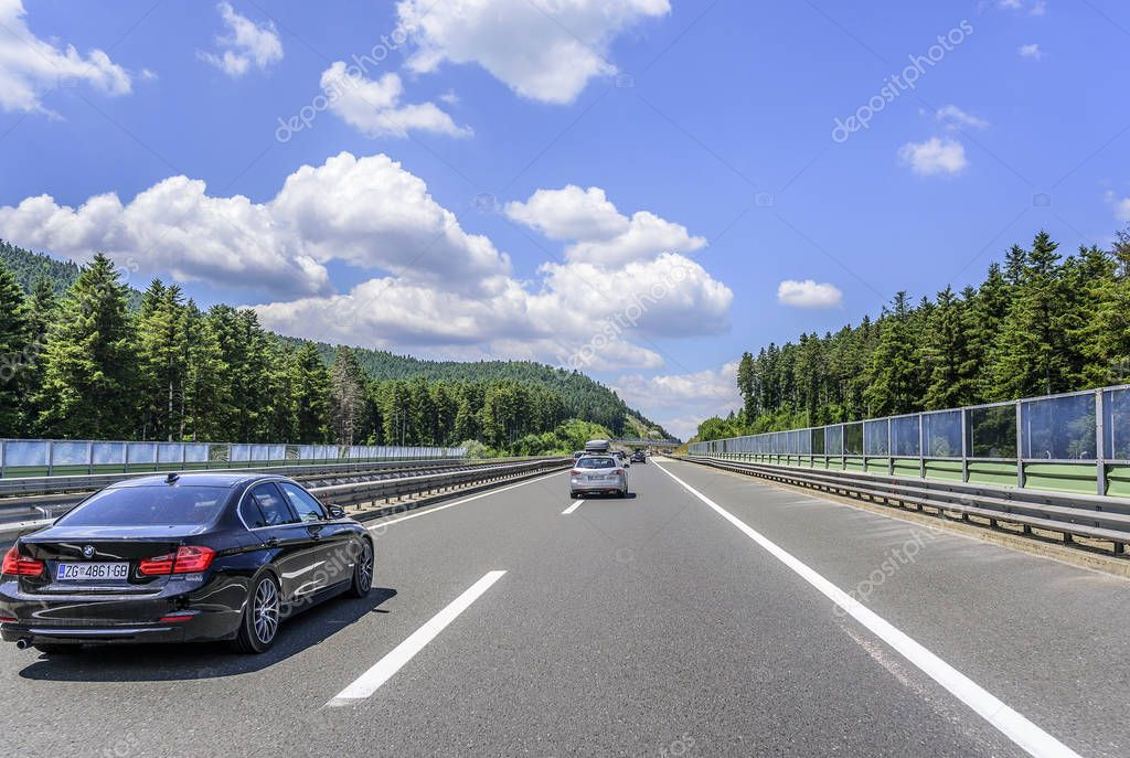 Cars speeding on the Autobahn among mountain scenery.