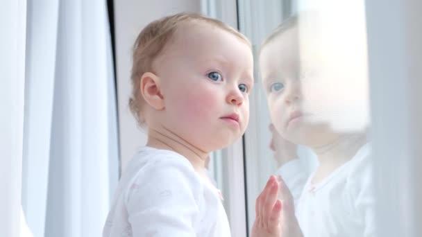 Kind blickt auf die Straße, die am Fenster steht.