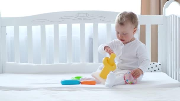 Baby dívka hrát s hračkami v posteli.