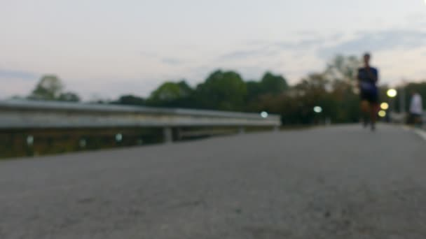 4K Blurred video Group of people running in a marathon. Street level close up of  runners feet.