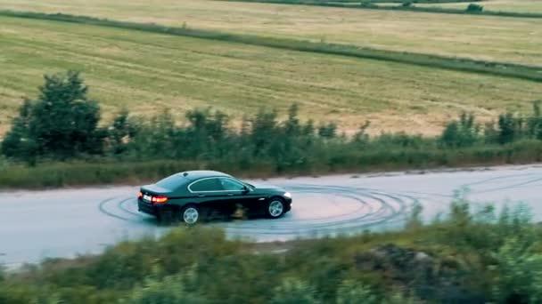 Černé bmw auto jedoucí po asfaltové silnici poblíž polí. Rusko. Výstřel dronů