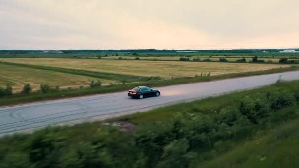 Dron sledující Bmw auto jedoucí po asfaltové cestě poblíž polí. Rusko.