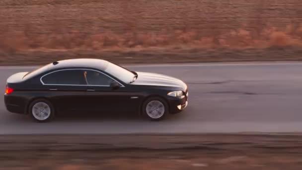 Bmw 5 černé auto jedoucí na silnici. Sluneční paprsky na obzoru. Petrohrad