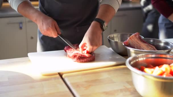 Koch in grauer Schürze schneidet Fleisch auf einem Plastikbrett. Nahaufnahme des kulinarischen Prozesses