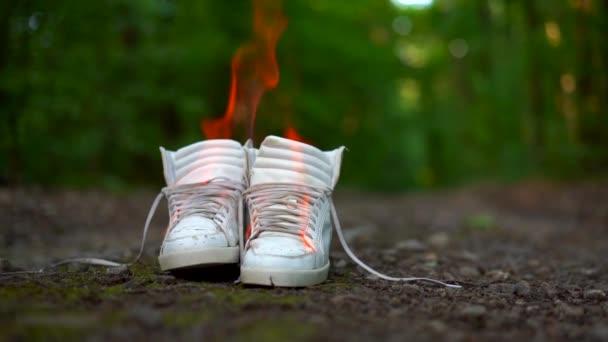 gebrauchte weiße Turnschuhe brennen auf einer Landstraße, die im Wald verläuft.