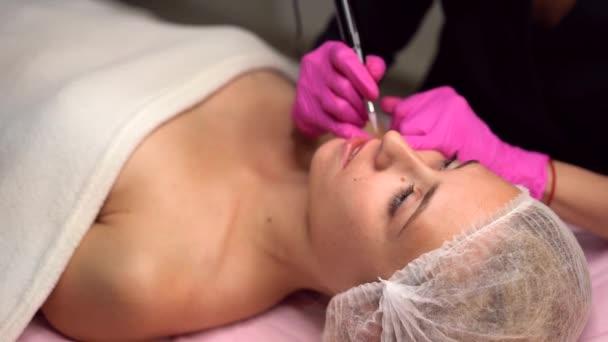 Arzt Kosmetologe tut Verfahren Permanent Make-up weibliche Client Lippen 4k