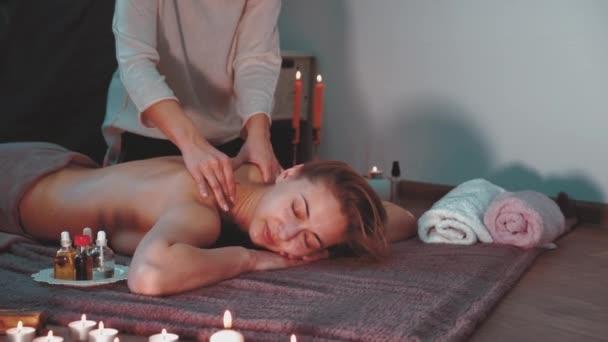 Odpočiňte si a užijte si v lázeňském salonu, při masáži profesionálním masérem. Žena ležící nahá záda relaxovat na podlaze přikrývky