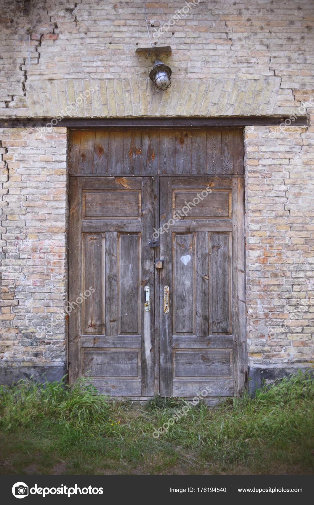 alte holztüren. eingang zur verlassenen gebäude aus ziegelstein