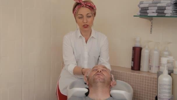 Fiatal nő fodrász egy kötés a fején a stílus pin-up mossa a haját, mielőtt vágja a férfi a székben. Beszélnek valamiről.