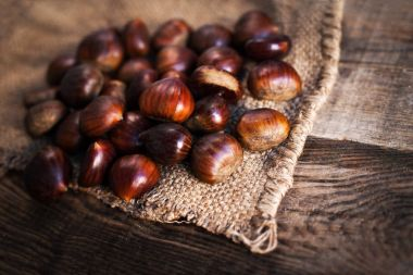 Ripe chestnuts on old wooden table
