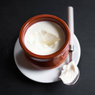 Sour  cream or natural  Cottage cheese curd in clay pot on dark  background. Traditional Cuajada yogurt cream