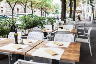 Street cafe with  tables and chairs. Cozy outdoor cafe. Dinner plate setting.