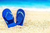 Fotografie Letní prázdninové beach pozadí s flip flops na tropické pláži. Pantofle z písku na pláži, relaxovat koncept